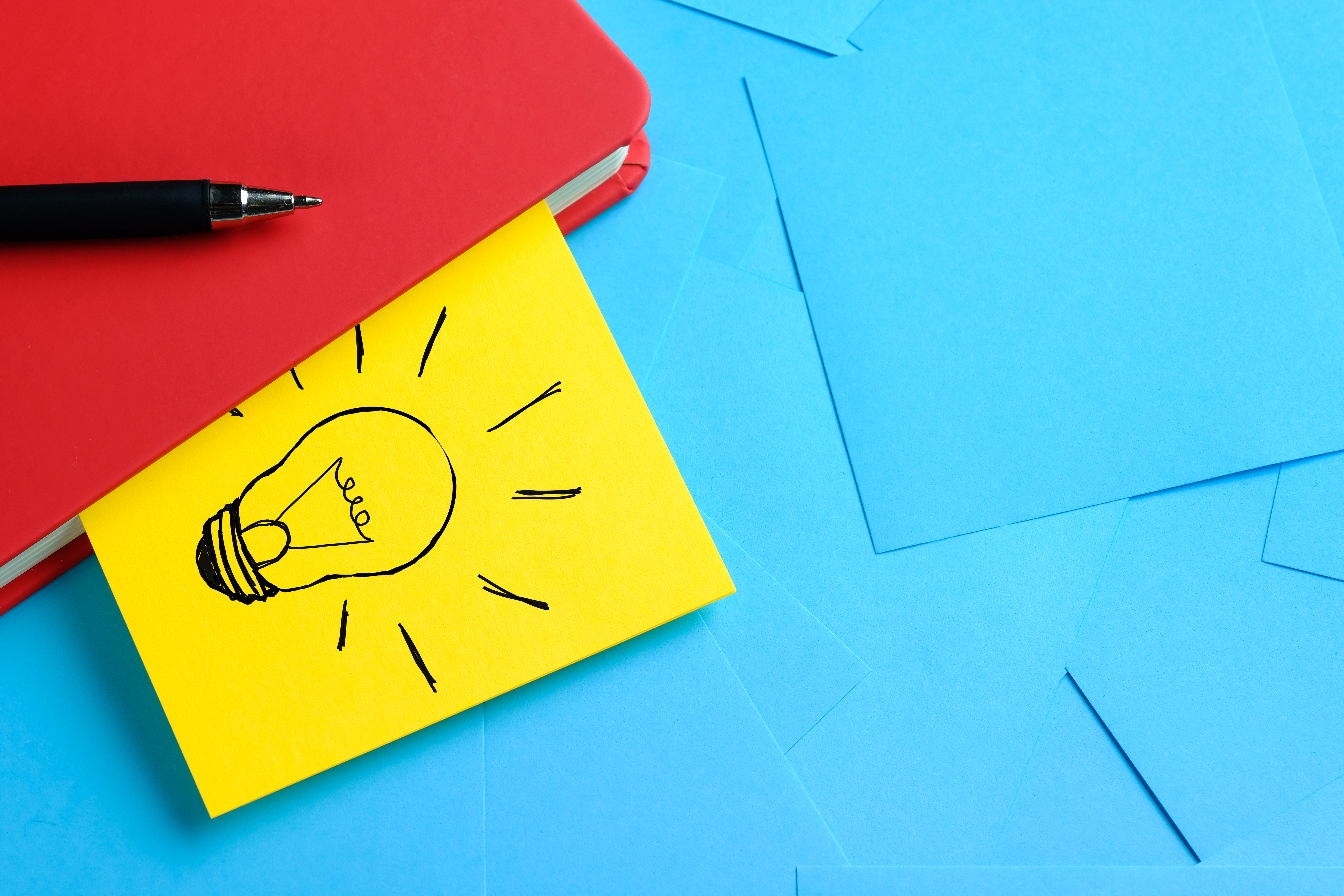 creative-drawing-light-bulb-yellow-sticker-attached-red-notepad-there-s-pen-it-concept-new-ideas-innovations-solutions-problems